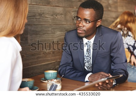 Team work: two corporate workers in formal wear sitting together at the table and discussing business plans. African man using digital tablet during a meeting with his Caucasian female colleague - stock photo