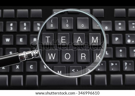 TEAM WORK written on keyboard with magnifying glass