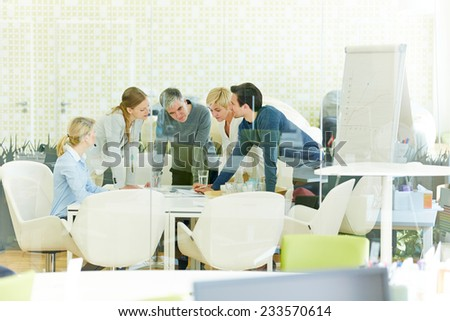 Team working together in office during a meeting - stock photo