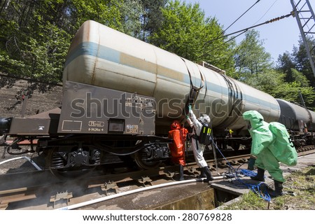 Team working with toxic acids and chemicals is securing train tanks crashed near Sofia, Bulgaria. Teams from Fire department are participating in a training with spilled toxic and flammable materials. - stock photo