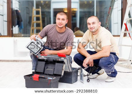 Teammate electricians with their tool boxes working in homes. - stock photo