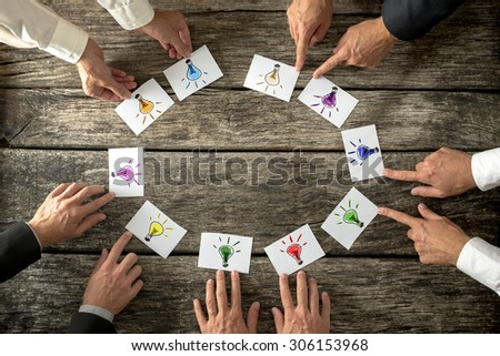 Teamwork and brainstorming concept with businessmen seated around a table each pointing to cards with colorful sketches of light bulbs conceptual of bright ideas and solutions arranged in a circle. - stock photo