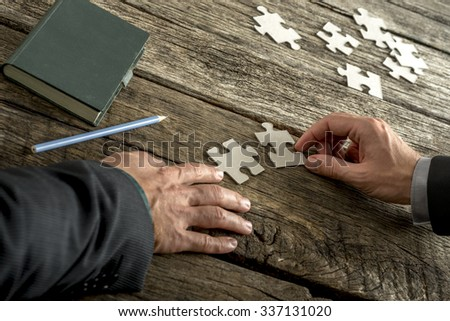 Teamwork and cooperation between two business people as they join forces to combine matching puzzle pieces on a textured rustic wooden desk with notepad and pencil alongside. - stock photo