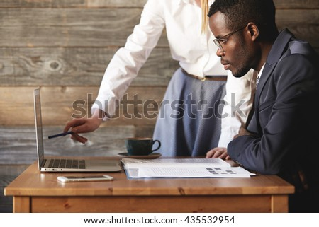 Teamwork and cooperation: two people working together on laptop in the office. Redhead Caucasian worker presenting a report to her African American director, holding a pen and pointing at the screen - stock photo