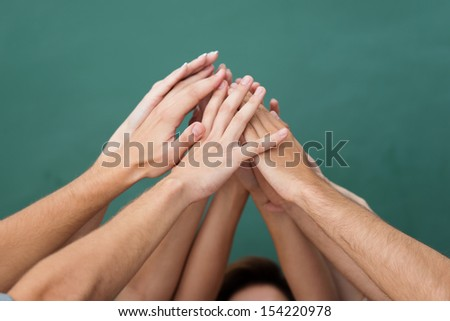 Teamwork and cooperation with a group of young people all raising their hands together and forming an overlapping pyramid, closeup view of their arms and hands - stock photo
