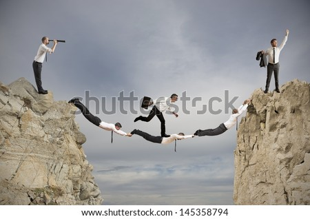 Teamwork and success concept with a bridge of businessperson - stock photo