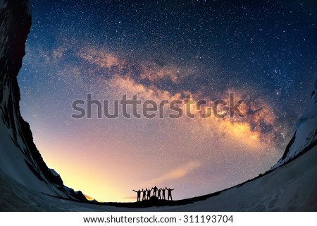 Teamwork and support. A group of people are standing together holding hands against the Milky Way in the mountains.  - stock photo