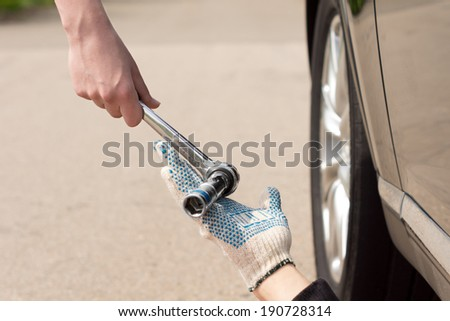 Teamwork as a mechanic fixing a car that has broken down at the side of a road is handed a steel socket wrench spanner by the female driver, close up view of their hands - stock photo