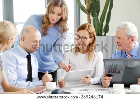 Teamwork at office. Businesswoman sitting at desk and holding digital tablet in her hands while consulting with business people at business meeting.
