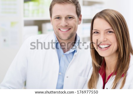 Teamwork at the pharmacy with a happy young male and female pharmacist smiling happily at the camera, close up of their faces - stock photo