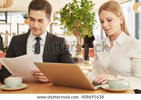 Teamwork. Beautiful young businesswoman working on her laptop while her male colleague is checking papers on a meeting in the restaurant - stock photo