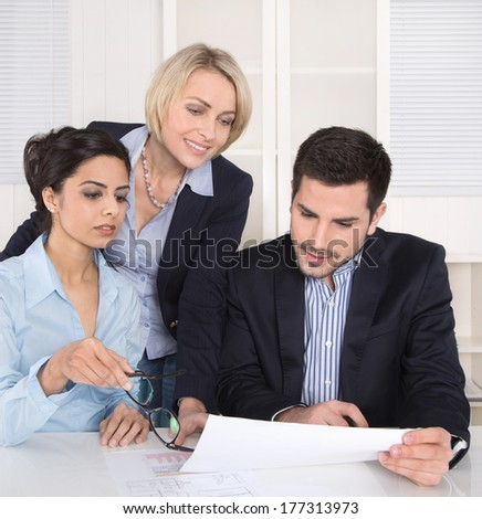Teamwork between three business people at desk at office.