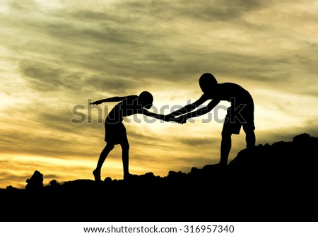 Teamwork boy hiking help each other trust assistance silhouette in mountains, sunset. - stock photo
