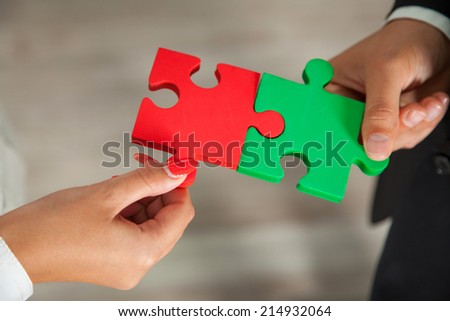 Teamwork - business people assembling jigsaw puzzle - stock photo