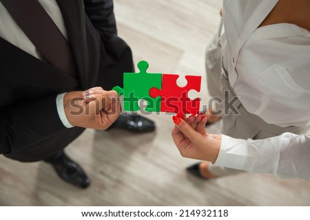 Teamwork - business people assembling jigsaw puzzle