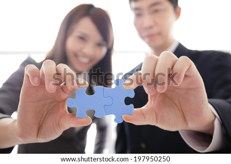 Teamwork - business people assembling jigsaw puzzle, asian - stock photo
