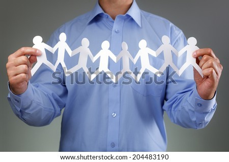 Teamwork,  community and support concept with businessman holding paper chain group of people holding hands - stock photo
