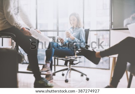 Teamwork concept, brainstorming. Businessman crew working with new startup project in modern loft. Woman holding smartphone hands. Horizontal, film effect