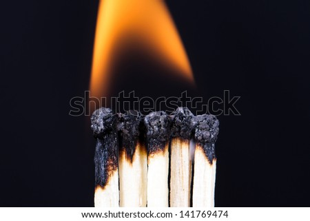 Teamwork concept, burning matches with flame on dark background.