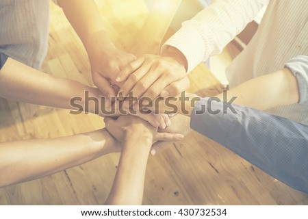 Teamwork concept,Business team standing hands together in the loft office.people joining hands for cooperation success business,win in every thing,vintage color - stock photo