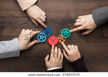 Teamwork concept. Different hands of men and women connect colorful gears into working mechanism on the brown wooden table background. Each has its own role in problem-solving. Experience exchange - stock photo