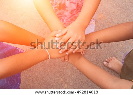 Teamwork concept. Group of children put their hands together.