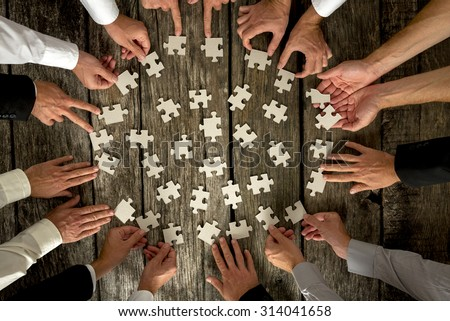 Teamwork Concept - High Angle View of Businessmen Hands Forming Circle and Holding Puzzle Pieces on Top of a Rustic Wooden Table. - stock photo
