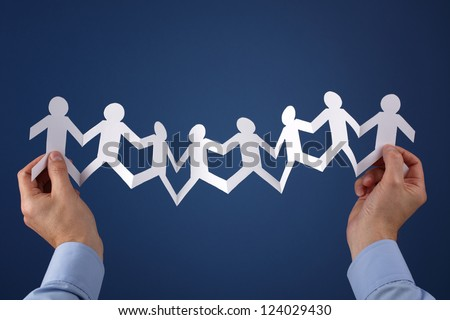 Teamwork concept with paper chain group of people holding hands held over blue background - stock photo
