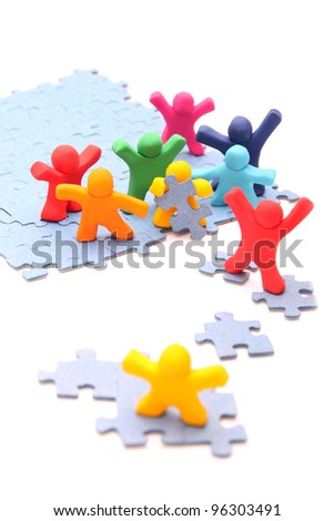 teamwork concept with plasticine people - colorful group is working together to save their little yellow fellow - isolated on white