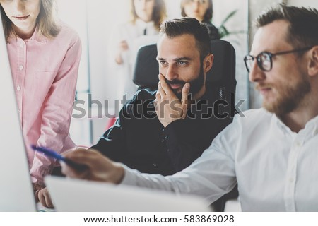 Teamwork concept.Young coworkers discussing new business project in modern office.Group of three people analyze reports on desktop computer.Horizontal,blurred background