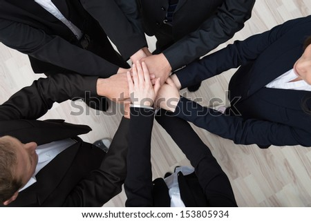 Teamwork - conceptual image of a group of young professional businesspeople standing in a circle facing each other clasping hands - stock photo