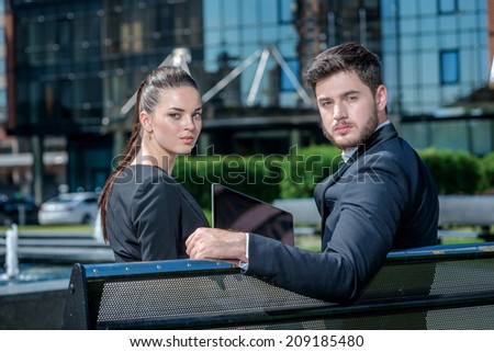 Teamwork. Confident businessman and successful business woman sitting on a bench and looks back - stock photo