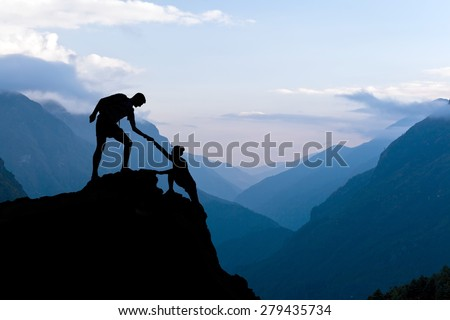 Teamwork couple helping hand trust assistance silhouette in mountains, sunset. Team of climbers man and woman hiker, help each other on top of mountain, beautiful landscape in Himalayas Nepal - stock photo