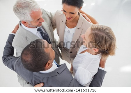 Teamwork embracing together in the workplace - stock photo