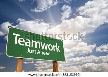 Teamwork Green Road Sign With Dramatic Clouds and Sky.