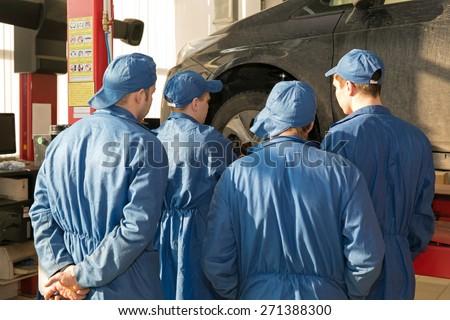 Teamwork: Group of Engineers and Mechanics People during Vehicle Suspension Repairing Works in Car Service Garage Workshop - stock photo