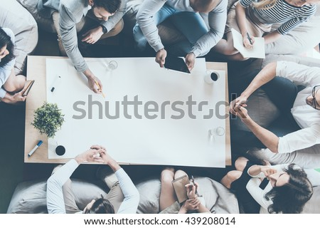 Teamwork in action. Directly above shot of business people sitting around desk and looking at copy space on large blank paper  - stock photo