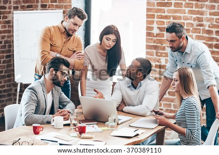 Teamwork in action. Group of six young people discuss something and gesturing while leaning to the tablein office - stock photo
