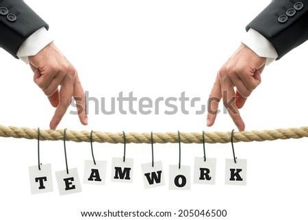 Teamwork in business concept with the letters spelling Teamwork individually suspended by wire from a rope with two men walking their fingers towards each other on top, over white. - stock photo