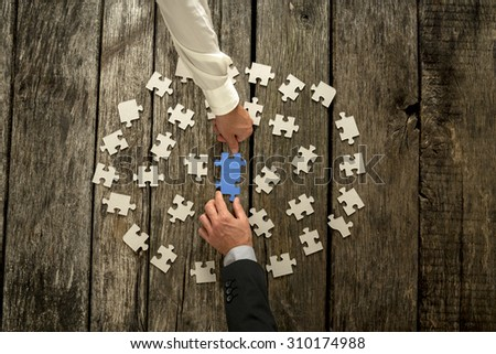 Teamwork in business concept with two businessmen around a circle of scattered white puzzle pieces cooperating to construct a blue jigsaw in the centre, close up of their hands and wooden table. - stock photo