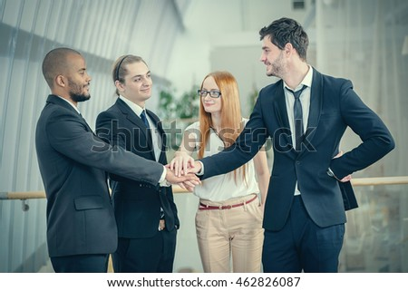 Teamwork in business. Four Confident businessman fold their arms tightly to each other in the office