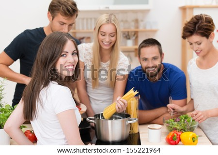 Teamwork in the kitchen with a group of happy young men and women gathered around a stove cooking spaghetti and salads - stock photo