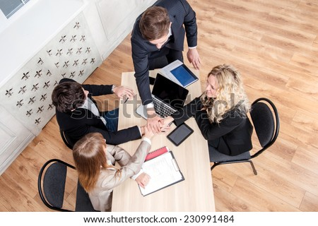 Teamwork in the office. Businessmen sitting at the table and discussing their business top view - stock photo