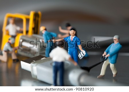 Teamwork In The Workplace. A team of miniature toy model artisans repairs data cables. - stock photo