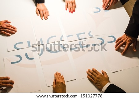 Teamwork means Success : Group of business people assembling the word success spread over several papers - one guy having problems fitting his piece into the right place.  - stock photo