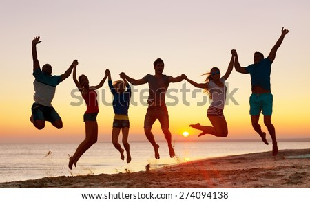 Teamwork. Multiracial Group of People Jumping at Beach, Backlight - stock photo