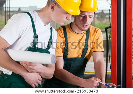 Teamwork of two professional factory engineers, horizontal - stock photo