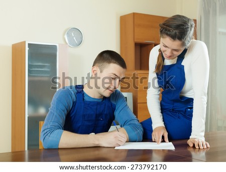 Teamwork of workers  in uniform wriring in questionnaire at table