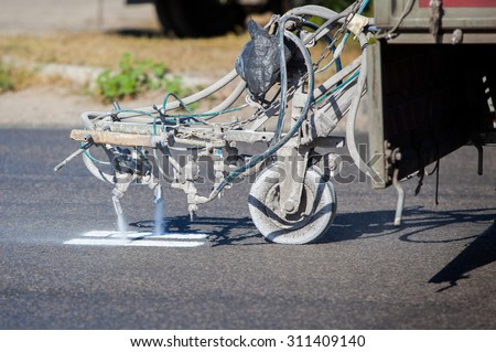 Teamwork: Pavement Asphalt Road Marking Paint and Striping with Thermoplastic Spray Applicator Machine during highway construction works. - stock photo