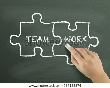 teamwork puzzle concept drawn by hand isolated on blackboard - stock photo